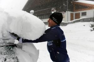 Tuomas Kotro mittaa uuden lumikerroksen syvyyttä.